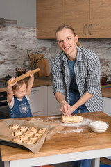 Father and child baking cinnabons on the kitchen with fun