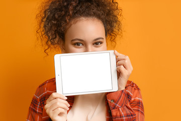 Beautiful young African-American woman with tablet computer on color background