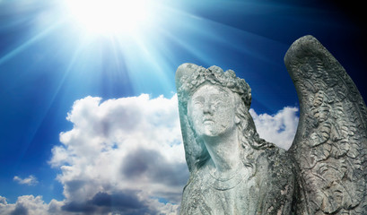 Fotomurales - Ancient stone statue of beautiful angel in the sunlight against blue sky. Horizontal image.