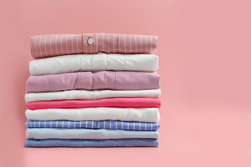 Stack of colorful perfectly folded clothing items. Pile of different pastel color shirts and...