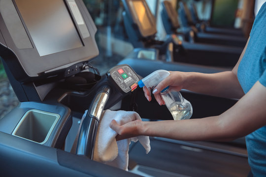 Gym cleaning and disinfection. Infection prevention and control of epidemic. Staff using wipe and alcohol sanitizer spray to clean treadmill in gym. Anti Covid-19 precautions