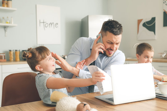 Little children keeping father from his work at home