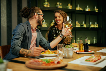 Young attractive caucasian couple sitting in restaurant and making at toast with white wine.