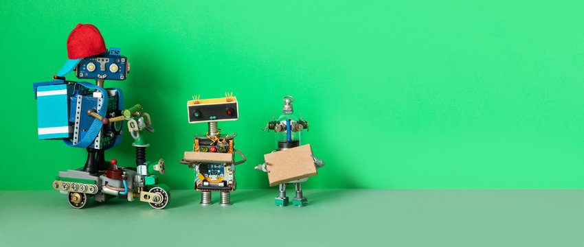 A robot courier delivered orders parcels to buyers. Two robots are holding cardboard boxes with food, possibly with pizza. Copy space for text.