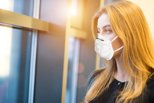 Masked business woman looking out of a window