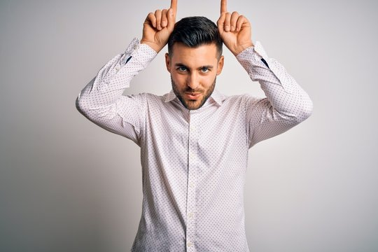 Young handsome man wearing elegant shirt standing over isolated white background doing funny gesture with finger over head as bull horns