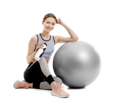 Sporty young woman with fitball and bottle of water on white background