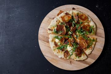 selbstgemachte Pizza mit Kräuterbutter, Mascarpone, Mozzarella, Rucola und Kartoffelchips, geschnitten, Studio