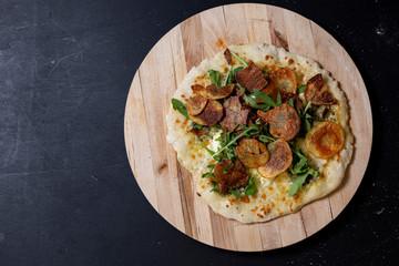 selbstgemachte Pizza mit Kräuterbutter, Mascarpone, Mozzarella, Rucola und Kartoffelchips, Studio