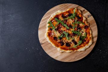 selbstgemachte Pizza mit Tomatensauce, Mozzarella, gebratener Speck und Zwiebeln, Rucola und Pinienkerne, Studio