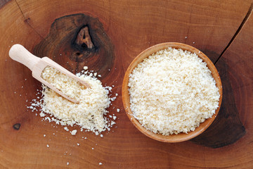 Almond flour in wooden bowl and scoop over wooden board top view