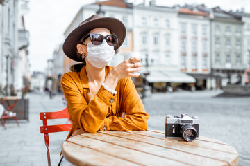 Young woman in facial mask sitting on the cafe terrace alone. Concept of social distancing and new...