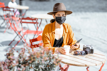 Portrait of a sad woman with despaired emotions in facial mask sitting on the cafe terrace alone. Concept of social distancing and new social rules after coronavirus pandemic.