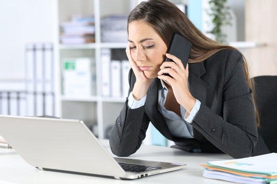 Executive calling on phone waiting on hold at office