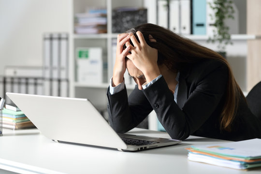 Sad executive complaining on her desk at the office