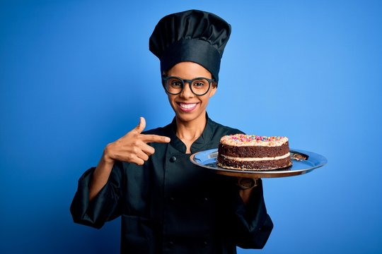 Young african american baker woman wearing cooker uniform and hat holding cake very happy pointing with hand and finger