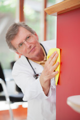 Mature doctor cleaning the furniture in his office