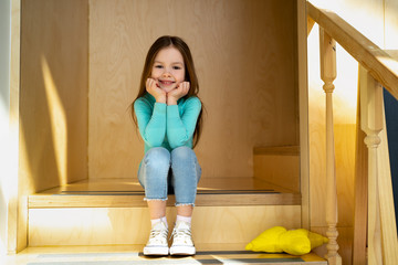 Cute little girl sitting on wooden steps at home