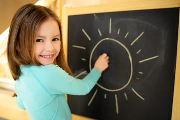 Joyful little girl drawing sun on chalkboard