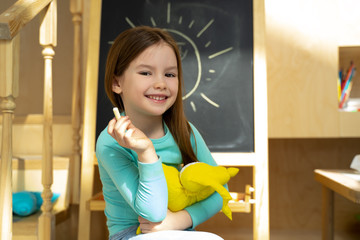 Cheerful little girl holding chalk and toy