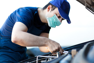 Photo sur cadre textile Pain Mechanic fixing a car engine wearing a mask, coronavirus concept
