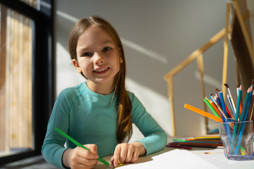 Cheerful little girl drawing with colored pencil at home
