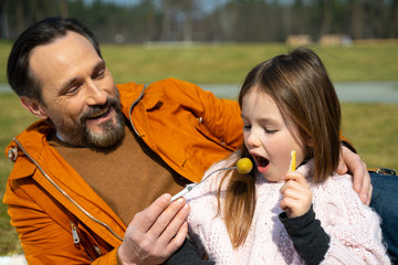 Cheerful father feeding his cute daughter with spoon