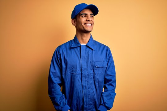 Young african american mechanic man wearing blue uniform and cap over yellow background looking away to side with smile on face, natural expression. Laughing confident.