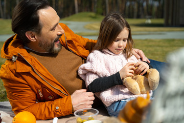 Loving father talking with upset daughter during picnic