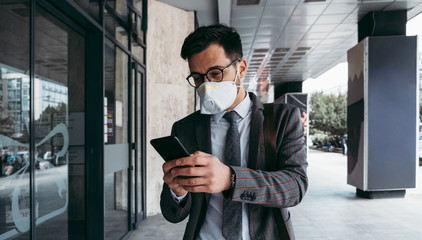 Business man with protective face mask using phone on city street.