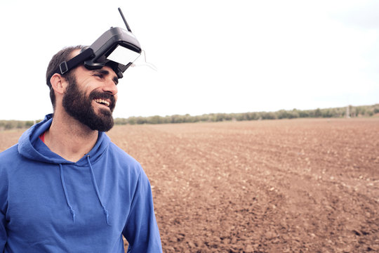 man smiles in the field with his 3d glasses after blowing up his drone