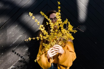 young woman holding forsythia in the sunshine