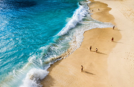 People on the beach on Bali, Indonesia. Vacation and adventure. Beach and large waves. Top view from drone at beach, azure sea and relax people. Travel and relax - image
