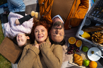 Happy family lying on blanket with food outdoors