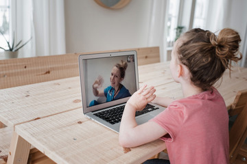 girl sat talking and waving to a nurse on a video call at home Wall mural
