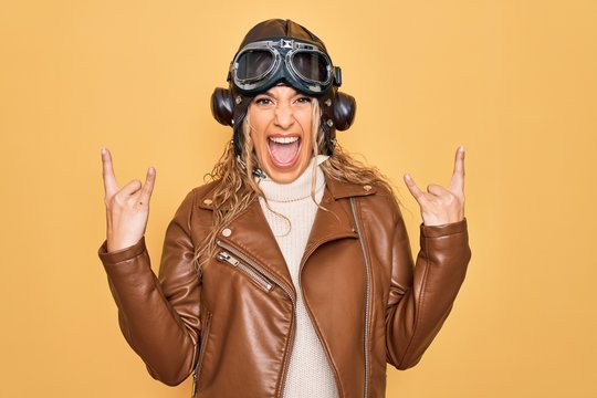 Young beautiful blonde aviator woman wearing vintage pilot helmet whit glasses and jacket shouting with crazy expression doing rock symbol with hands up. Music star. Heavy concept.