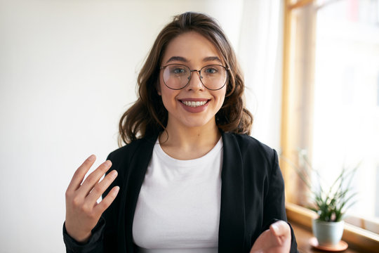 Beautiful positive young woman blogger recording course or workshop for her followers. Cute girl in eyewear chatting from home making video call using webcam and wirelesshigh speed internet connection