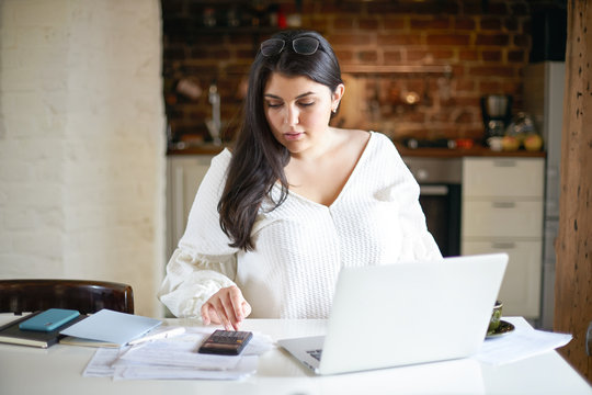 Focused plus size young female accountant filing in documentation sitting at kitchen table, working as freelancer from home, calculating expenses, taxes, making financial annual report, using laptop