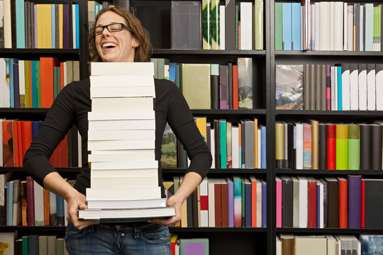 woman carrying stack of books in bookstore