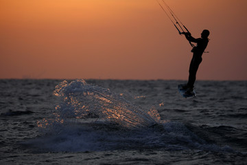 A man surfs with his kitesurfing board in the Mediterranean sea in Ashkelon as restrictions following the coronavirus disease (COVID-19) ease around Israel