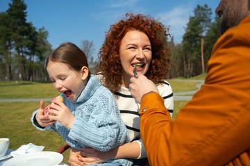 Joyful woman enjoying breakfast with husband and daughter