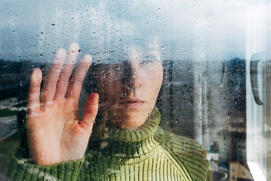 Melancholic young woman looking through window