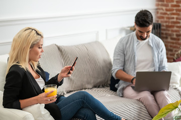 Positive blonde woman with cup of juice browsing smartphone and sitting on couch near ethnic boyfriend typing on laptop keyboard in living room of modern apartment
