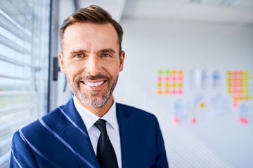 Portrait of happy entrepreneur, manager in suit smiling at modern office