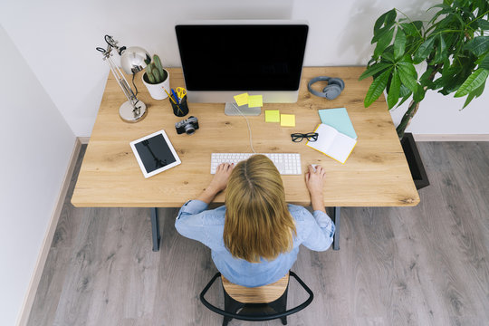 Blonde Caucasian woman works from her home office