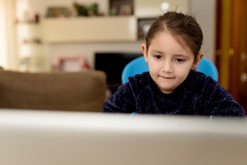 Cute girl sitting at table and focusing on laptop screen while listening to teacher during online lesson at home