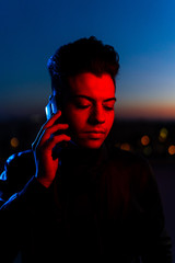 Serious modern man in black jacket talking on smartphone while standing in red and blue light looking down on the street with dark blue sky in background