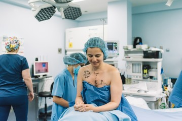 Blurred surgeon using photo camera to shoot breast of female patient before performing mammoplasty in modern hospital