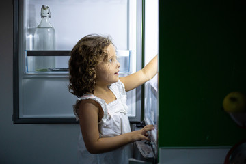 Little girl in sleepwear searching for snack inside open refrigerator at night in kitchen at home
