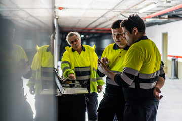Group of skilled male engineers in uniform using gadgets while examining electrical equipment in modern building
